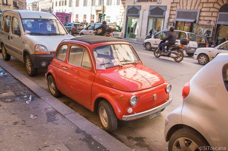 Bildet viser en gammel rød Fiat 500 parkert i ei bygate. Andre biler er parkert foran og bak. I gata kjører bilder og scootere forbi.