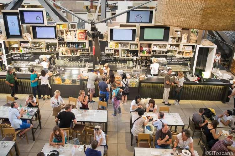 Bildet viser folk som sitter og spiser ved bordene på ett av spisestedene i Matmarkedet Mercato Centrale i Firenze.