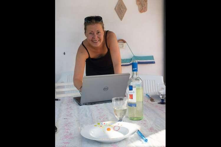 Bildet viser Karine Angell som står på en terrasse utenfor et feriehus i Toscana og jobber på PC.