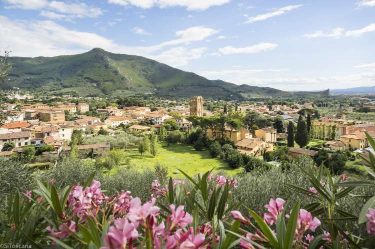 Bildet viser utsikten fra åssiden ovenfor Calci. Du ser landsbyens bebyggelse med kirketårnet i sentrum. På andre siden ser du fjelltoppen La Verruca.
