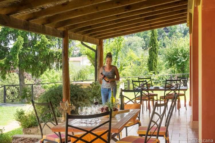 Bildet viser kvinne som dekker opp et bord på en terrasse for vinsmaking. Feriebostedet La Pergola ved Lari i Toscana.