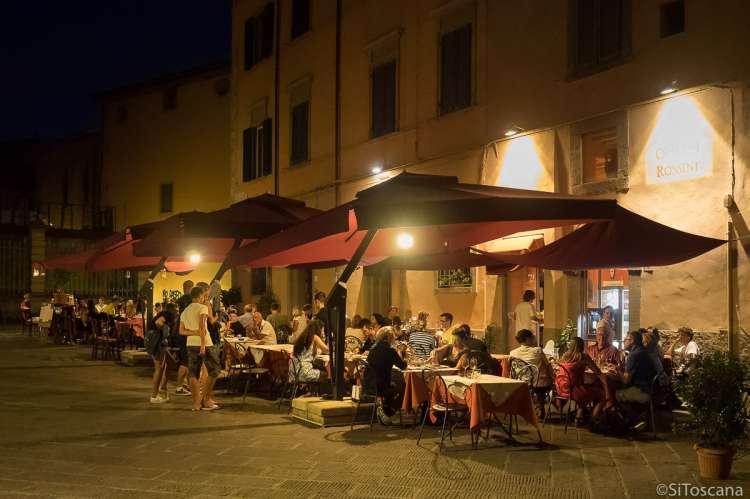 Bildet viser folk som sitter ute og spiser på en av restaurantene på Piazza Dante Alighieri i Pisa. Bildet er tatt en varm sommerkveld og det er mørkt.