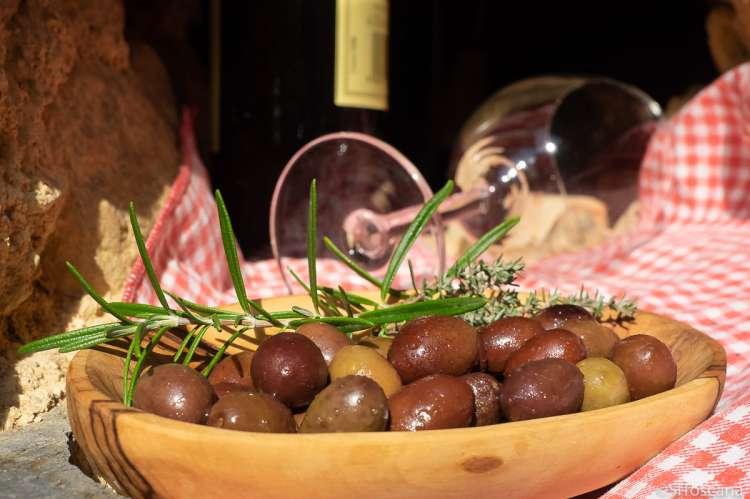 Bildet viser et fat fullt av oliven. Fatet er av tre og står på en rødrutete duk. I bakgrunnen ligger et vinglass. Bildet er fra Montemagno ved Pisa, Toscana.