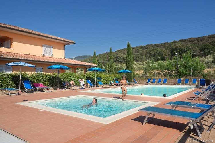Bildet viser barnebasseng og stort basseng for voksne på residensen Vicino Mare ved sjøen i Toscana.
