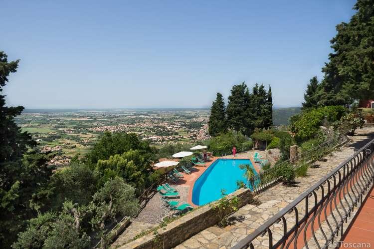 Fantastisk utsikt utover landskapet i Toscana og kysten ved Middelhavet. Svømmebassenget med solsenger og parasoller. Foto.