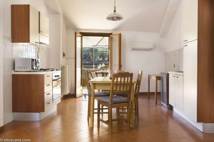 Foto av oppholdsrom med kjøkken, spisebord og utgang til terrasse i ferieleiligheten Marco i sentrum av Firenze, Florence..