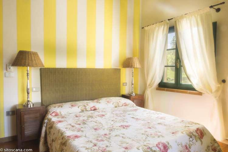 Bildet viser dobbeltsengen i soverommet i leiligheten Ginestra på feriebostedet Girasole, vingård med 10 leiligheter og gangavstand til landsby.