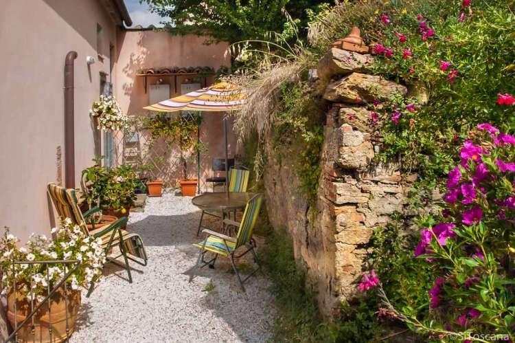 Foto av uteplassen til ferieleiligehten for 2-3 personer. Terrasse med utemøbler og parasoll.
