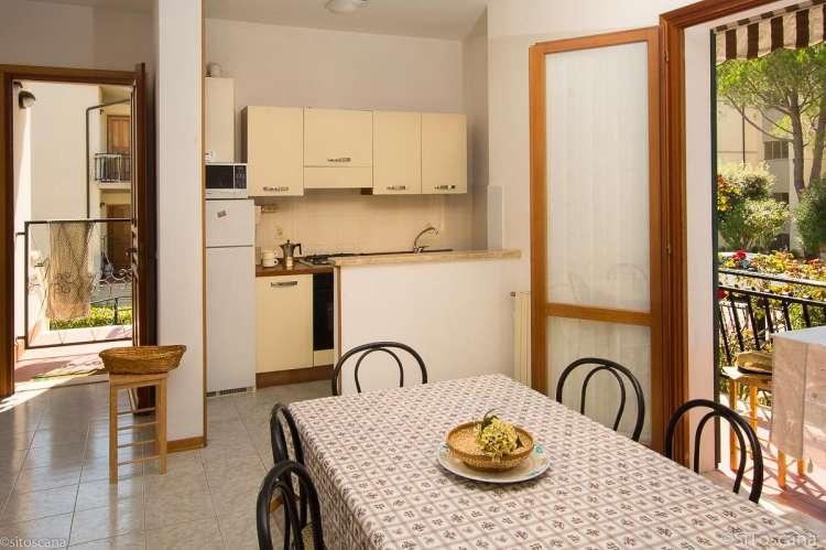 Bildet viser oppholdsrom med kjøkken og utgang til balkong i ferieleiligheten Vito al Mare i Castiglioncello.