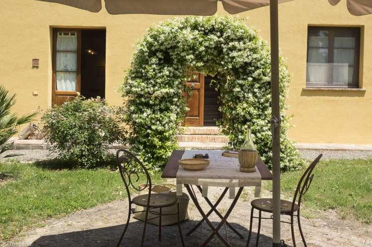 Foto av uteplassen til ferieleilighet på vingård i Toscana. La Bella Lavanderina med portal av blomster i hagen.