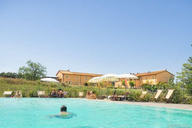 Bilde av gjester som leier ferieleilighet på vingården og nyter sol og sommer ved bassenget i Toscana.
