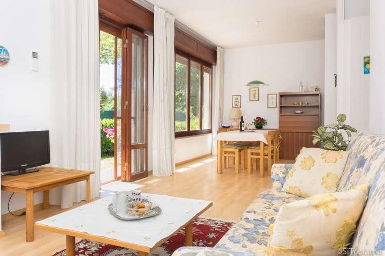 Bildet viser stue med sofa og spisebord i ferieleiligheten Marco i Buganvilla ved havet.
