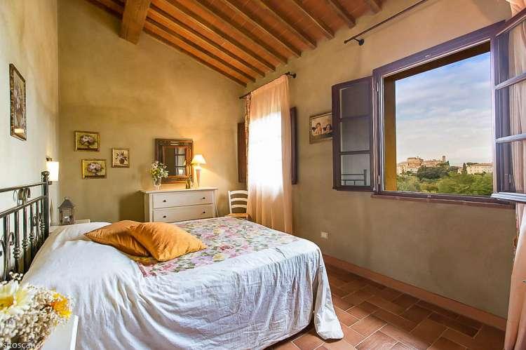 Bildet viser soverom med dobbeltseng og vindu med utsikt i ferieleiligheten Nespola på La Pergola i Toscana.