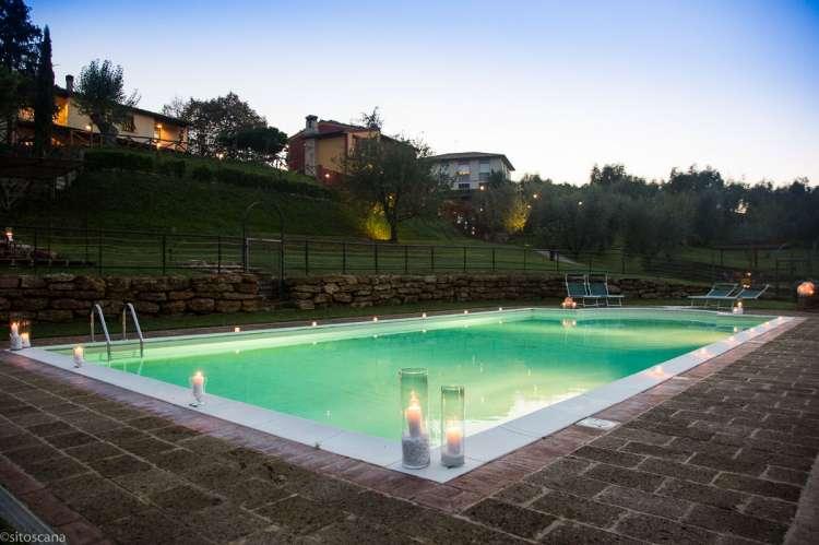 Bildet viser bassenget med levende lys på kanten, i skumringen om kvelden. På feriebostedet La Pergola ved Lari i Toscana.