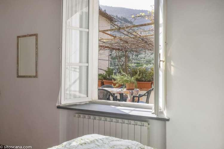 Ett av de fire soverommene i ferieleiligheten Terrazza. Vindu mot terrassen. Foto.