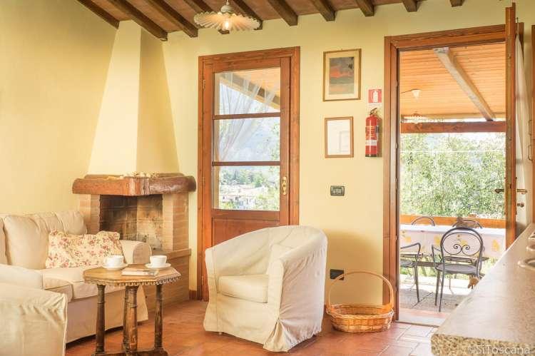 Bildet viser sofa, lenestoler og dør ut til terrasse i feriehuset Villa Verde.