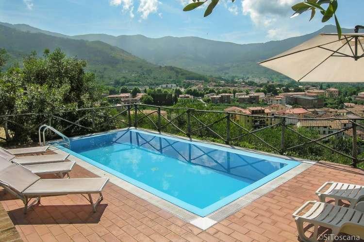 Bildet viser basseng med solstoler og utsikt fra feriehuset Villa Vista ved Pisa.