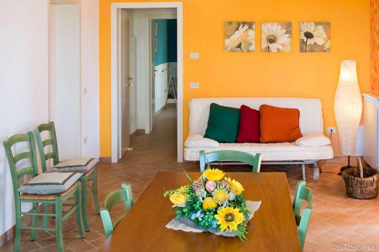 Bildet viser stoler, spisebord, sovesofa og gul vegg i ferieleiligheten Tinaia på olivengården Vivaio. Kjempefint for småbarnsfamilier.