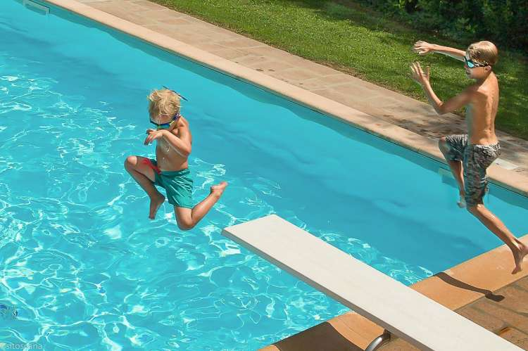 Bildet viser barn i full aktivitet i svømmebassenget, på stupebrett på vingården Borgo Etruschi sentralt i Toscana.