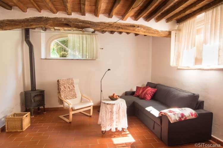 Bilde av stua med god dobbel sovesofa og typisk toskansk byggestil i ferieleiligheten Karine.. Vedovn til bruk i den kjølige sesongen.