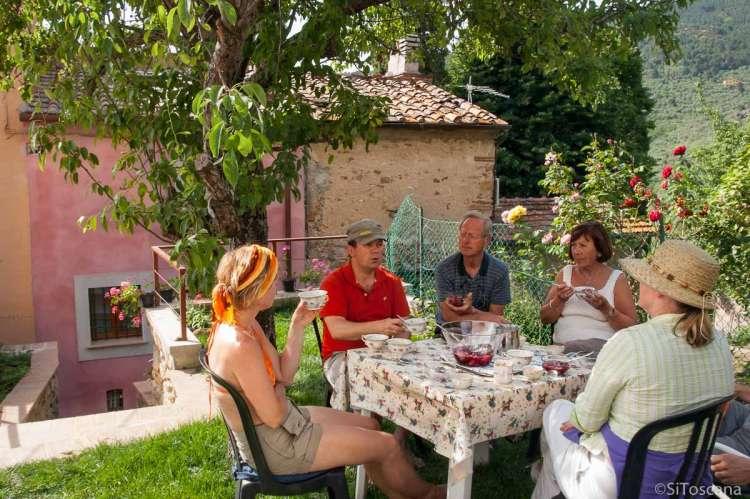 Spiseplass under pæretreet i hagen. Familegruppe gjester sim leier feriehus i landsby i Toscana. Bilde.