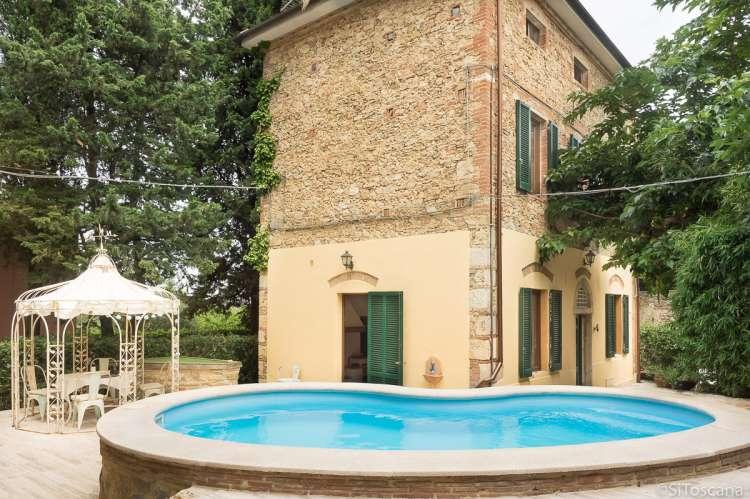 Bildet viser feriehus med terrasse og basseng i landsby i Toscana.