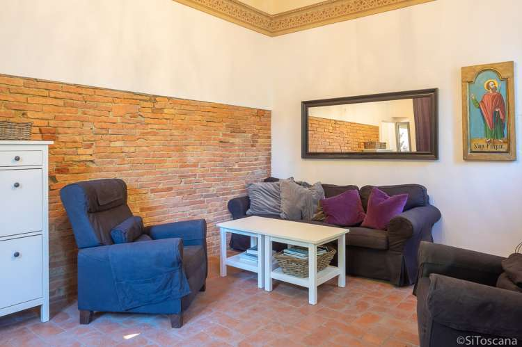 Bildet viser stue med sofa i ferievilla i landsby i Toscana.