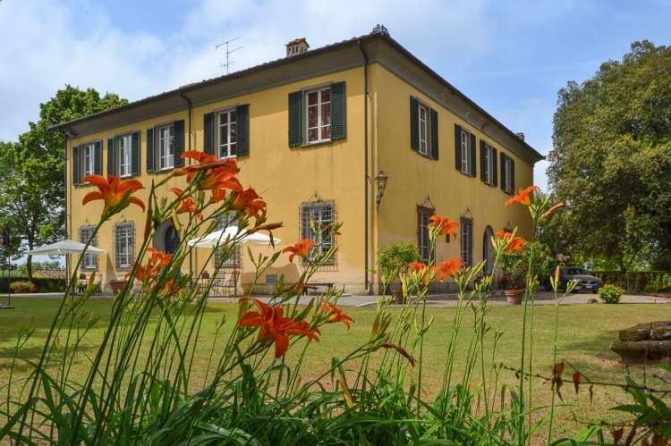 Bildet viser stor villa ved landsby i Toscana.