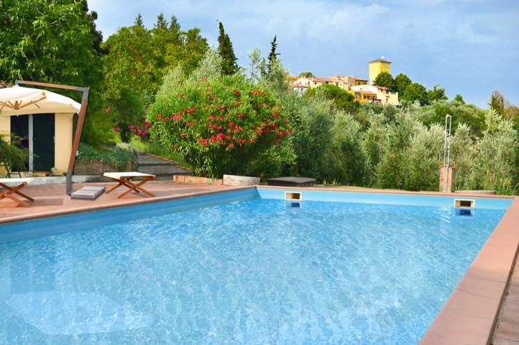 Bildet viser bassenget i Villa Alba og utsikt mot nærmeste landsby som ligger i gangavstand fra villaen. Ved bassengkanten står det en parasoll og stoler.