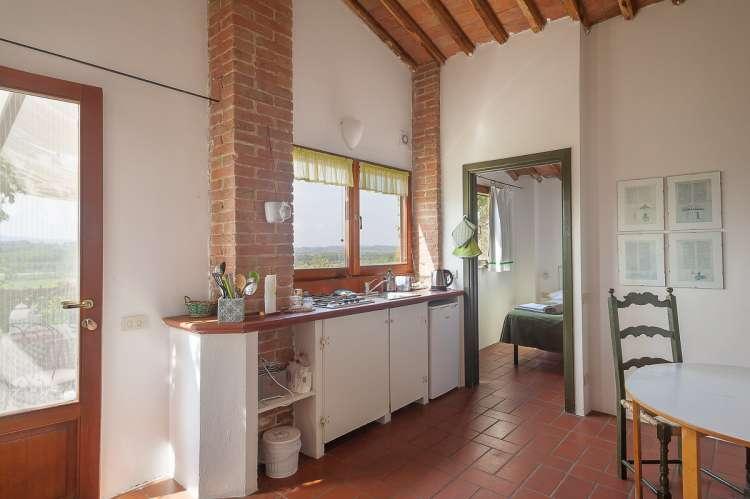 Bildet viser kjøkken med utsikt i feriebolig på olivengård i Toscana.