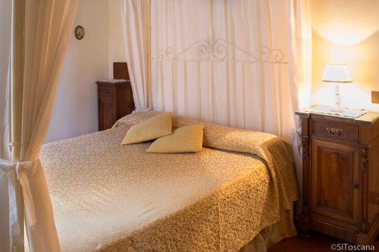 Foto av soverom med dobbeltseng og nattbord i toskansk stil i ferieleiligheten Giallo.
