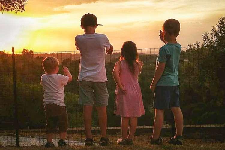 Bildet viser barn som ser på solnedgangen i vakkert kveldslys. Barna er få ferie i  Toscana.