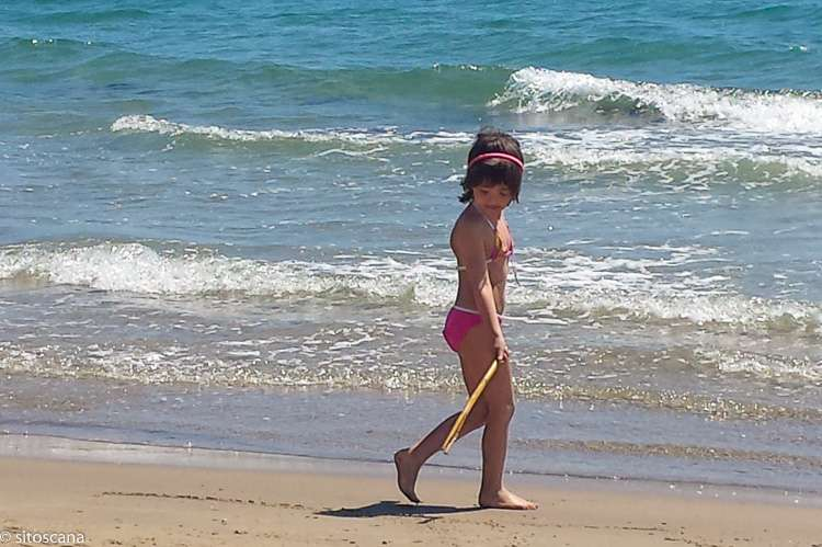 Bildet viser et barn som leker på stranden. Bildet er brukt på websiden sitoscana.no som kategoribilde til kategorien: Bo i gangavstand til strand.