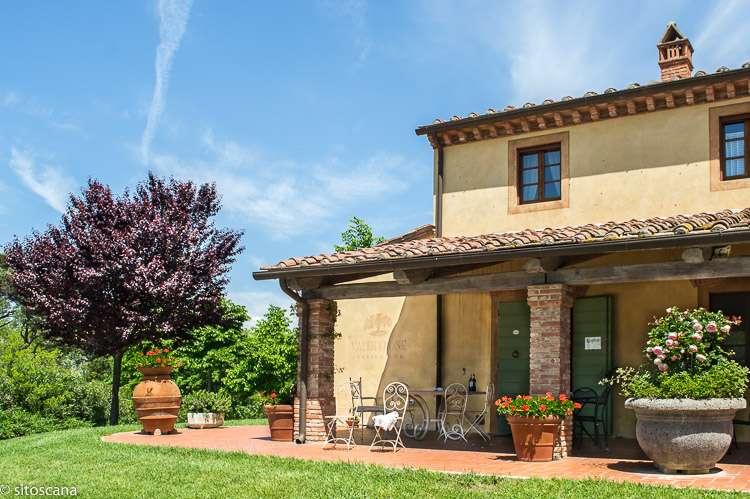 Bildet viser del av en villa med plen, blomster og terrasse i Toscana, Italia. Bildet er brukt som illustrasjon på kategorien Bo i Villa eller hus på websiden sitoscana.no