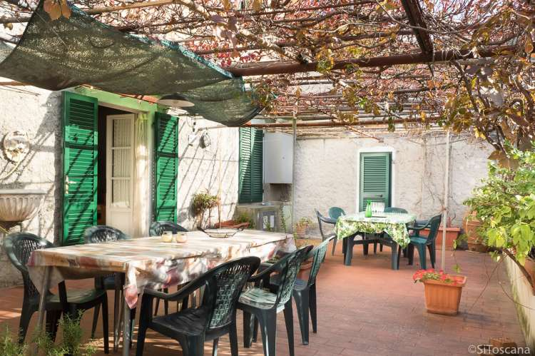 Bildet viser stor terrasse under pergola i feriehuset Terrazza i landsby i Toscana.