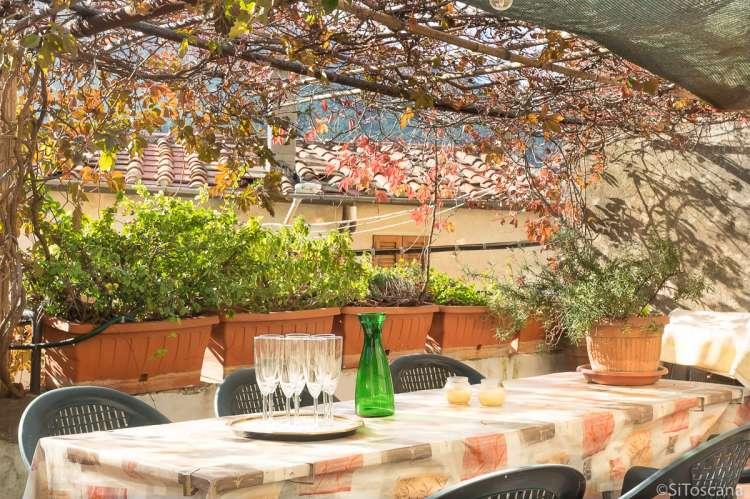 Bildet viser spisesbord på terrasse i ferieleilighet i landsby i Toscana.