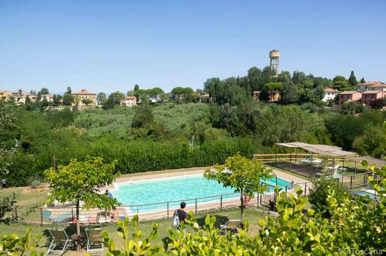 Bildet viser basseng med utsikt mot toskansk landsby.