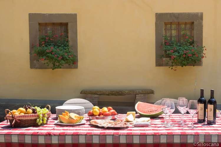 Bildet viser langbord utenfor villa med basseng i Toscana.