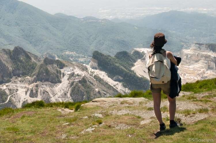 Bildet viser en kvinne på tur som nyter utsikten mot marmorfjellene. SiToscana formidler ferieboliger som egner seg når man vil nyte friluftsliv med gåturer og sykkelturer.