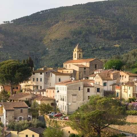 Bildet viser middelalderlandsbyen Montemagno ved Pisa i Toscana. Du ser en del av bebyggelsen som er gamle steinhus, den 100 år gamle kirka. Bak landsbyen ser du åsene rundt.