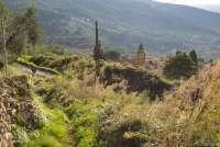Bildet viser en av de skiltete turstiene som har utgangspunkt i middelalderlandsbyen Montemagno. Man ser kirka Santa Maria ad Nives som ligger øverst i landsbyen. I bakgrunnen skimter man Pisa og Middelhavet.
