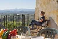 Bildet viser Karine Angell som nyter utsikten fra feriehuset Canonica på vingården Borgo Etruschi.