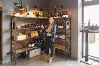 Bildet viser Karine Angell som kjøper vin på vingården Torre a Cenaia. Det er hyller med vin og delikatesser.