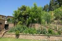 Bildet viser en grønnsakshage i Toscana. Gamle steinhus og murer i bakgrunnen.